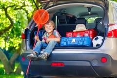 Peu de garçon d'enfant s'asseyant dans le tronc de voiture juste avant partir pour le vaca Photographie stock libre de droits