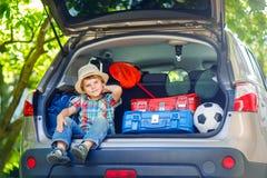 Peu de garçon d'enfant s'asseyant dans le tronc de voiture juste avant partir pour le vaca Image libre de droits