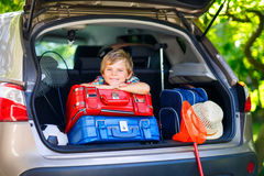 Peu de garçon d'enfant s'asseyant dans le tronc de voiture juste avant partir pour le vaca Images libres de droits