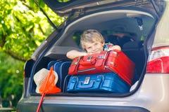 Peu de garçon d'enfant s'asseyant dans le tronc de voiture juste avant partir pour le vaca Photo stock