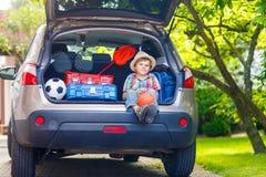 Peu de garçon d'enfant s'asseyant dans le tronc de voiture juste avant partir pour le vaca Photos libres de droits