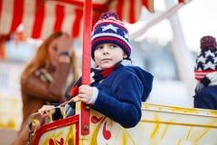 Peu de garçon d'enfant sur la roue de ferris sur le marché de Noël Images stock