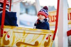 Peu de garçon d'enfant sur la roue de ferris sur le marché de Noël Photographie stock