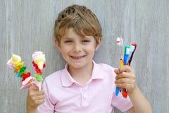 Peu de garçon d'enfant tenant la brochette de guimauve dans une main et des brosses à dents dans des autres Images libres de droits