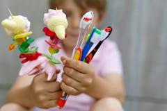 Peu de garçon d'enfant tenant la brochette de guimauve dans une main et des brosses à dents dans des autres Photo libre de droits