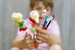Peu de garçon d'enfant tenant la brochette de guimauve dans une main et des brosses à dents dans des autres Images stock