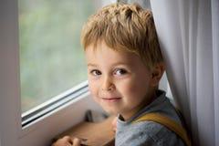 Peu de garçon d'enfant tenant la fenêtre proche et le sourire Image stock