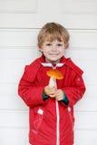Peu de garçon d'enfant tenant le grand champignon dans des mains Image stock
