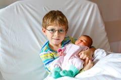 Peu de garçon d'enfant tenant sa soeur nouveau-née de sommeil de bébé dans l'hôpital Images libres de droits