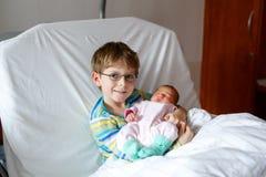 Peu de garçon d'enfant tenant sa soeur nouveau-née de sommeil de bébé dans l'hôpital Photo stock