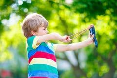 Peu de garçon d'enfant tirant la fronde en bois photographie stock
