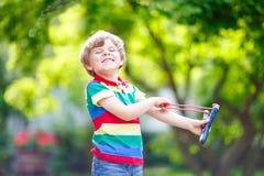Peu de garçon d'enfant tirant la fronde en bois photo stock