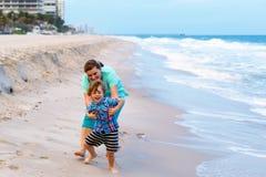Peu de garçon et mère d'enfant sur la plage de l'océan Image stock