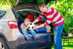 Peu de garçon et père d'enfant avant de partir pour des vacances de voiture Images libres de droits