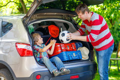 Peu de garçon et père d'enfant avant de partir pour des vacances de voiture Photo stock