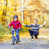 Peu de garçon et père d'enfant avec la bicyclette dans la forêt d'automne Image libre de droits