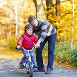 Peu de garçon et père d'enfant avec la bicyclette dans la forêt d'automne Photographie stock