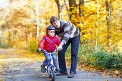 Peu de garçon et père d'enfant avec la bicyclette en automne Image libre de droits