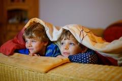 Peu de garçons d'enfant regardant la télévision et appréciant des bandes dessinées Photo stock