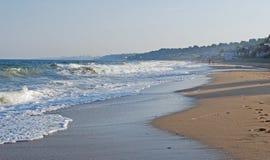 Peu de gens ayant l'amusement sur la plage orageuse Photographie stock libre de droits