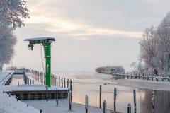 Peu de grue verte dans un petit port à un lac pendant l'hiver Photos libres de droits