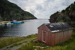 Peu de hutte rouge le long d'un littoral rocailleux à la crique de bouteille dans Terre-Neuve Images libres de droits