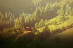 Peu de maison sur une pente de montagne verte Images libres de droits