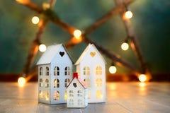 Peu de maisons de Noël de jouet avec un intérieur brûlant de lumière est sur le fond vert blured Photographie stock libre de droits