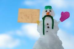 Peu de message de carte de papier de bonhomme de neige de Noël heureux extérieur. Hiver. Photographie stock
