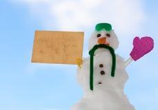 Peu de message de carte de papier de bonhomme de neige de Noël heureux extérieur. Hiver. Photographie stock libre de droits