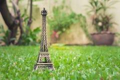 Peu de modèle de Tour Eiffel sur l'herbe verte dans le jardin extérieur avec le fond de lumière du soleil Photographie stock libre de droits