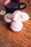 Peu de morceaux de guimauve rose et d'un thé de tasse sur le backgroun en bois Photo stock