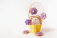 Peu de Pâques est sur une écharpe de fête Les oeufs de pâques multicolores se situent dans un panier avec le pain d'épice de déco Photographie stock