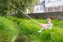 Peu de pêche de garçon d'enfant sur la rivière avec la canne à pêche selfmade Photographie stock