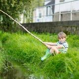 Peu de pêche de garçon d'enfant sur la rivière avec la canne à pêche selfmade Photos libres de droits