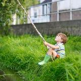 Peu de pêche de garçon d'enfant sur la rivière avec la canne à pêche selfmade Photographie stock libre de droits