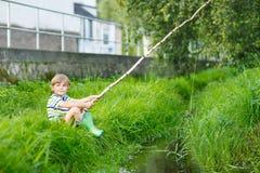 Peu de pêche de garçon d'enfant sur la rivière avec la canne à pêche selfmade Images libres de droits
