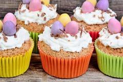 Peu de petits gâteaux de Pâques avec des oeufs de pâques et givrage sur le fond en bois Photographie stock libre de droits