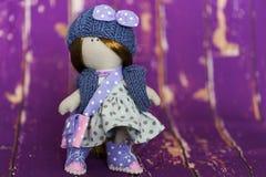 Peu de poupée de chiffon habillée dans la robe bleu-clair de point de polka, bleu a tricoté le chapeau avec l'arc Photographie stock