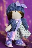 Peu de poupée de chiffon habillée dans la robe bleu-clair de point de polka, bleu a tricoté le chapeau avec l'arc Photo stock