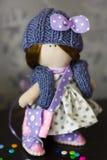 Peu de poupée de chiffon habillée dans la robe bleu-clair de point de polka, bleu a tricoté le chapeau avec l'arc, Photo libre de droits