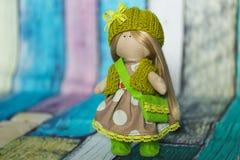 Peu de poupée de chiffon habillée dans la robe brun clair de point de polka, chapeau tricoté vert avec l'arc de dentelle, gilet t Photo libre de droits