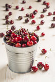 Peu de seau en laiton de cerises sur une table Photo libre de droits