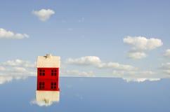 Peu de symbole rouge de maison sur le miroir Image stock