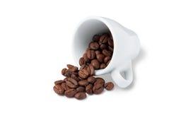 Peu de tasse avec les grains de café dispersés se trouvant sur le blanc Photographie stock