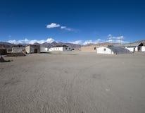 Peu de vieilles maisons, de montagnes rocheuses et de vallée roussie sur un backgro Image stock
