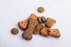 Peu des aliments pour chiens et des festins sur une surface blanche images stock