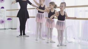 Peu des filles ont la le?on de ballet classique apprenant des mouvements de jambe avec le professeur dans le studio d'art banque de vidéos