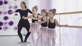 Peu des filles ont la le?on de ballet classique apprenant des mouvements de jambe avec le professeur dans le studio d'art clips vidéos