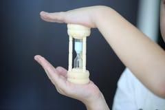 Peu des mains tiennent le sablier élégant avec le sable bleu dans eux, concept de valeur temps photo libre de droits